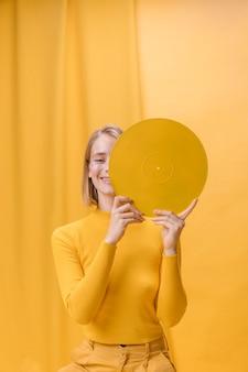 Vrouw met vinyl voor gezicht in een gele scène