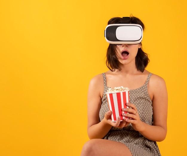 Vrouw met virtual reality-bril en popcorn