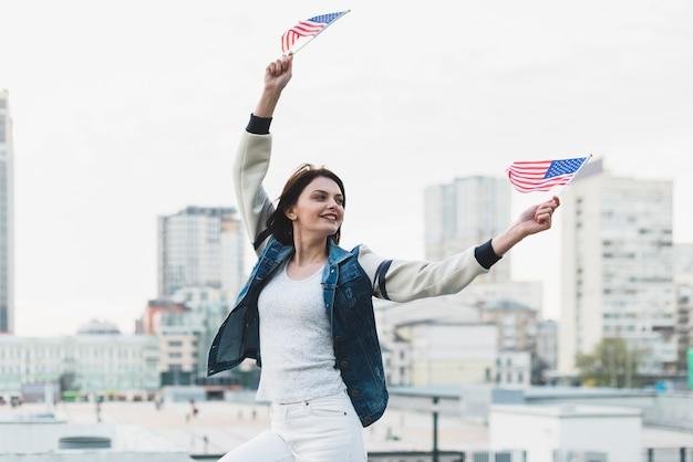 Vrouw met vlaggen op independence day of america zwaaien