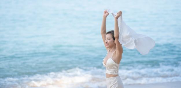 Vrouw met vliegende sjaal of shirt in handen joggen op het oceaanstrand. genieten van de zomer.