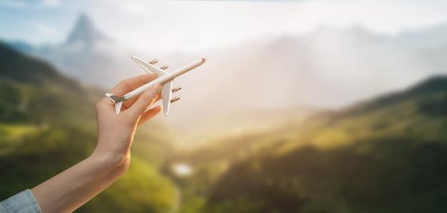 Vrouw met vliegtuig in handen en vliegen over de zonsondergang achtergrond