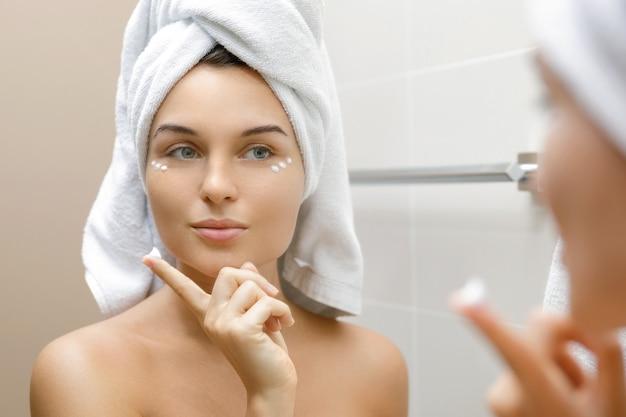 Vrouw met vochtinbrengende en anti-aging crème onder haar ogen