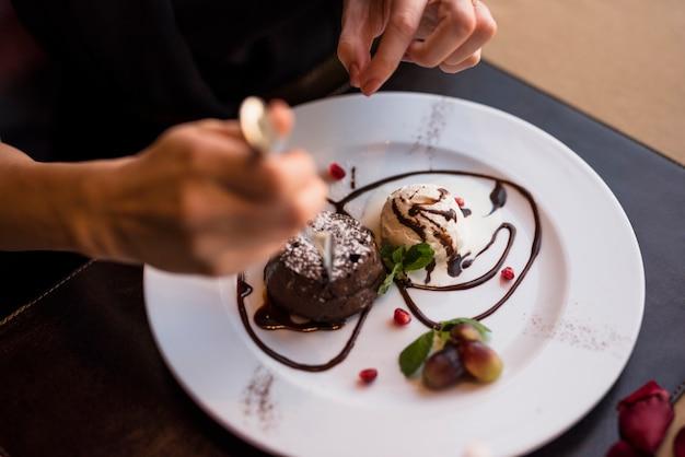 Vrouw met vork en heerlijk vers chocoladedessert in restaurant