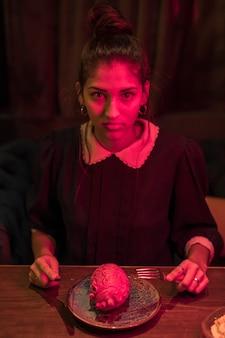 Vrouw met vork en mes aan tafel met een model van het hart op de plaat