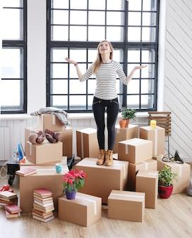 Vrouw met vrachtpakketten klaar voor verzending of verhuizing, gelukkig voelen