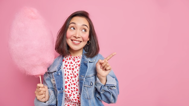 Vrouw met vrolijke uitdrukking glimlacht aangenaam wijst weg op kopieerruimte toont richting houdt heerlijke suikerspin draagt spijkerjasje