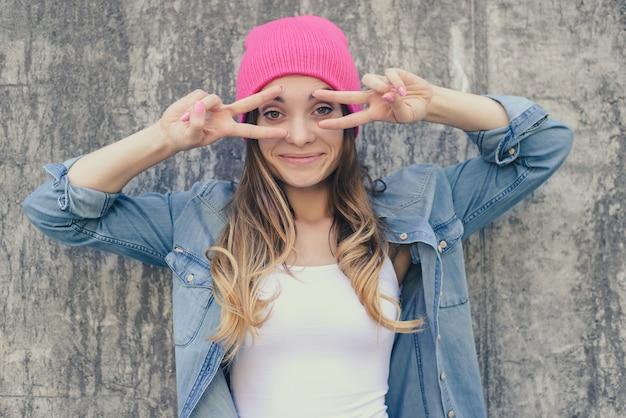Vrouw met vsign in de buurt van ogen grijze muur achtergrond
