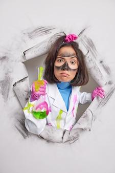 Vrouw met vuil gezicht houdt fles met kleurrijke vloeistof vast en draagt witte jas rubberen handschoenen breekt door papier