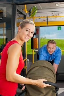 Vrouw met wandelwagen die in een bus krijgt
