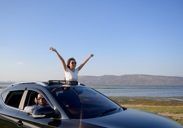 Vrouw met wapens het uitgestrekte duidelijk uitkomen van zonnedak van auto