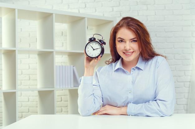 Vrouw met wekker bij lijst in bureau