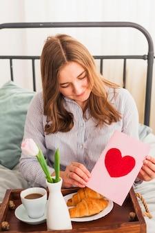Vrouw met wenskaart met hart tekenen