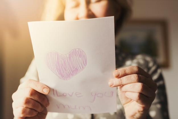 Vrouw met wenskaart met ik hou van je moeder inscriptie
