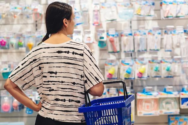 Vrouw met winkelmandje. moeder kiest een pasgeboren babyproduct in de supermarkt. zwangerschap en winkelen. vrouw die babyspullen kiest in de winkel van de babywinkel.