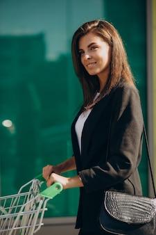 Vrouw met winkelwagentje bij supermarkt