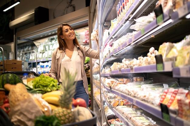 Vrouw met winkelwagentje eten bij supermarkt kopen