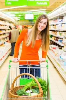 Vrouw met winkelwagentje in de supermarkt