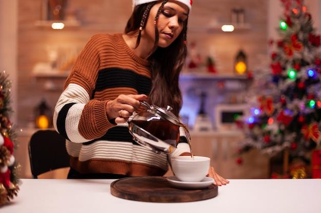 Vrouw met winterkleren die een kopje thee uit de waterkoker giet