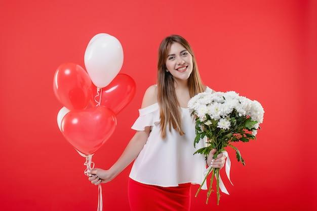 Vrouw met wit bloemboeket en hart gevormde die ballons op rode muur worden geïsoleerd