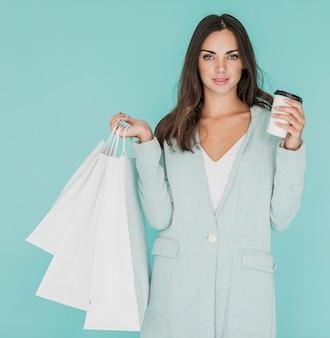 Vrouw met witte boodschappentassen en koffie