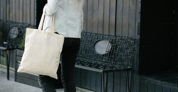 Vrouw met witte eco-textielzak tegen de achtergrond van de stedelijke stad. . ecologie of milieubescherming concept. witte eco-tas voor mock-up.