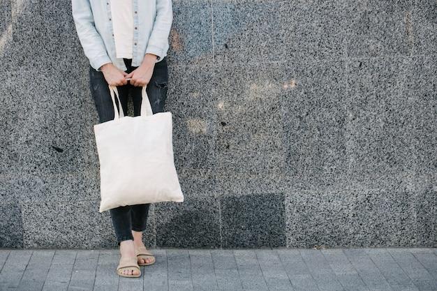 Vrouw met witte eco textielzak tegen de achtergrond van de stedelijke stad. ecologie of milieubescherming concept. witte eco-tas voor mock-up.
