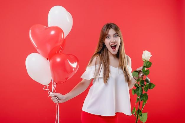 Vrouw met witte roos en hartvormige ballonnen geïsoleerd over rode muur