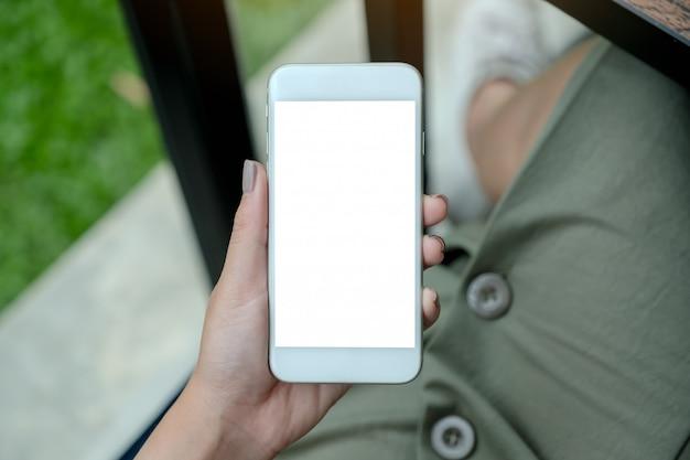 Vrouw met witte slimme telefoon met lege desktop-scherm
