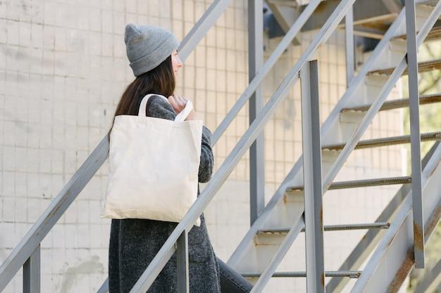 Vrouw met witte textiel totalisator eco tas in stedelijk gebied