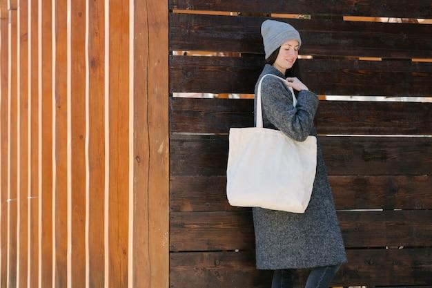 Vrouw met witte textiel totalisator eco tas in stedelijk gebied Premium Foto