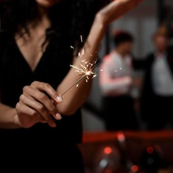 Vrouw met wonderkaarsen op oudejaarsavondfeest