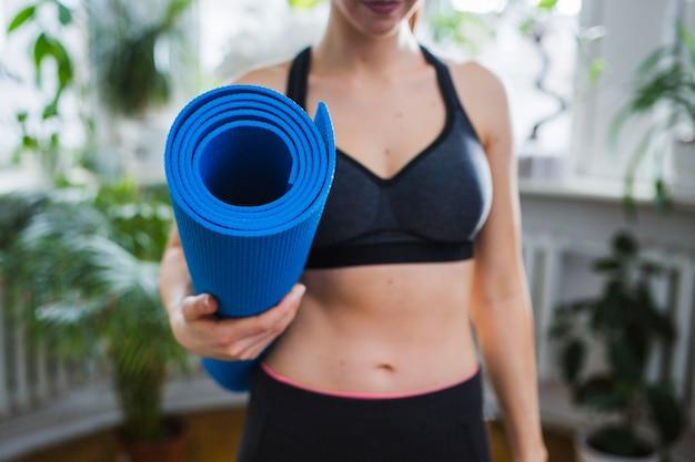 Vrouw met yoga mat bijsnijden