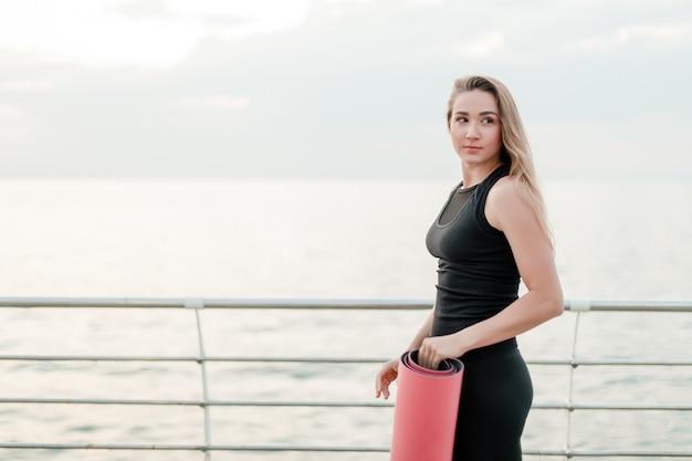 Vrouw met yogamat komt naar de zee om asana te oefenen bij zonsopgang