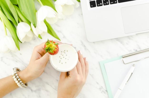 Vrouw met yoghurt drankje in de buurt van de laptop