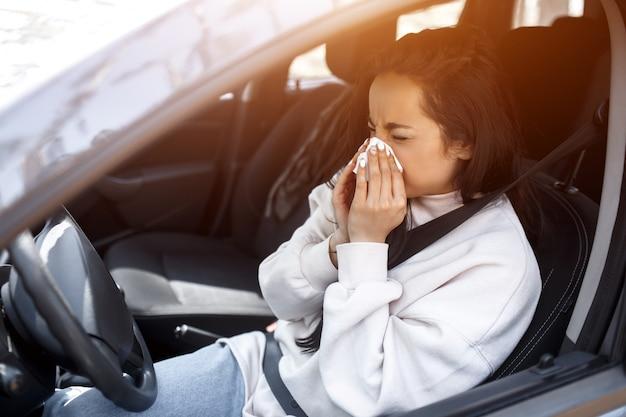 Vrouw met zakdoek. ziek meisje heeft loopneus. vrouwelijk model is een remedie tegen verkoudheid in de auto