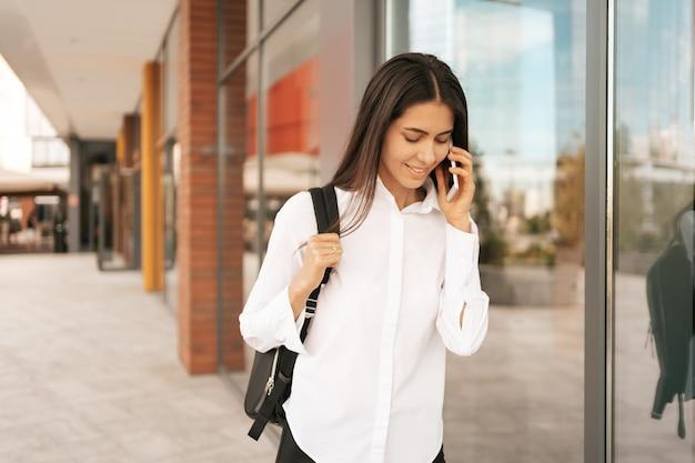 Vrouw met zakelijke rugzak die loopt terwijl ze aan het telefoneren is in de buurt van een zakelijk gebouw