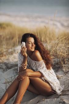 Vrouw met zeeschelp op het strand tijdens vakanties