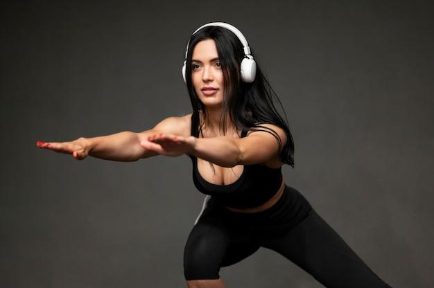 Vrouw met zich hoofdtelefoon het uitrekken