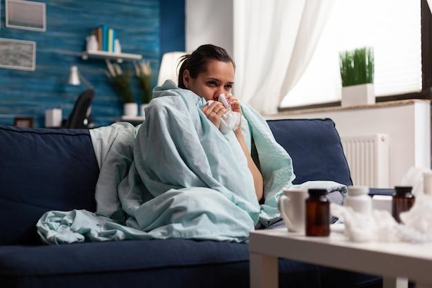 Vrouw met ziekte thuis in een deken gewikkeld ziek gevoel onwel jonge blanke volwassene die lijdt aan...