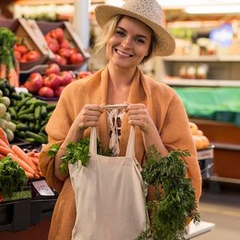 Vrouw met zomerhoed bij de boodschappen glimlacht