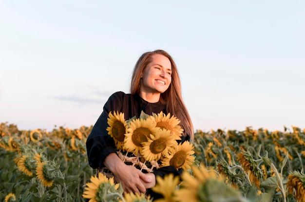 Vrouw met zonnebloemen lage hoek