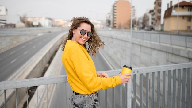 Vrouw met zonnebril die zich op een brug bevindt