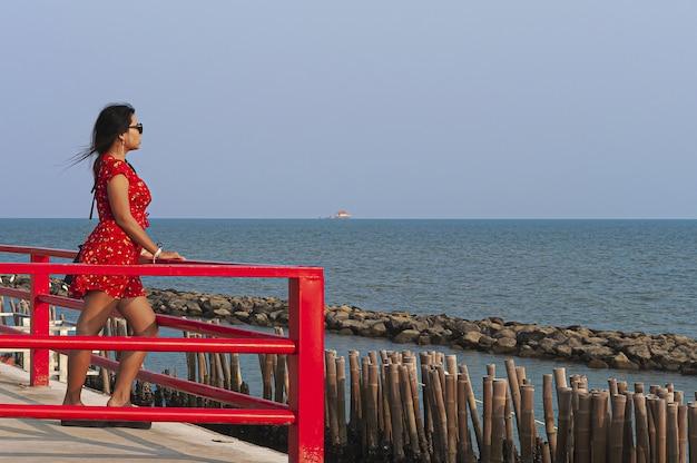 Vrouw met zonnebril en een rode jurk staande op de red boardwalk-brug in thailand
