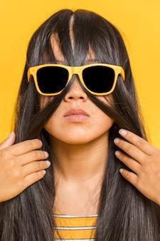 Vrouw met zonnebril en haar op haar gezicht