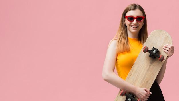 Vrouw met zonnebril en skateboard