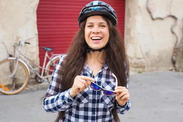 Vrouw met zonnebril op de achtergrond fiets en rode deur.