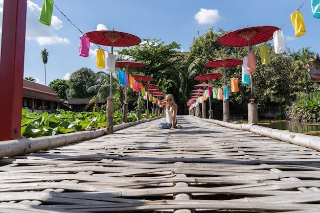 Vrouw met zonnebril zit in het midden van een houten brug met gekleurde paraplu's