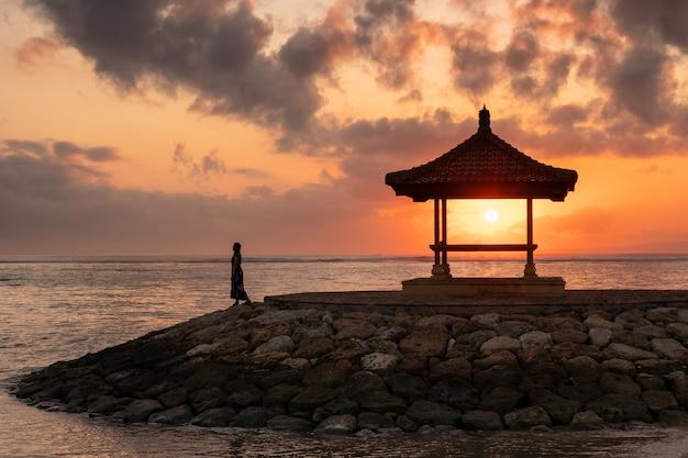 Vrouw met zonneschijn in paviljoen op pier bij kustlijn