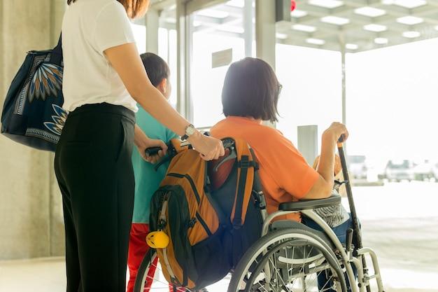 Vrouw met zoon en moeder in rolstoel die op het inschepen bij internationale luchthaven wachten.