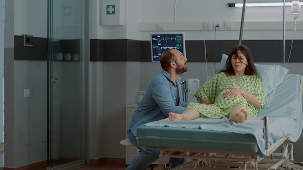 Vrouw met zwangerschap en pijnlijke weeën in ziekenhuisafdeling
